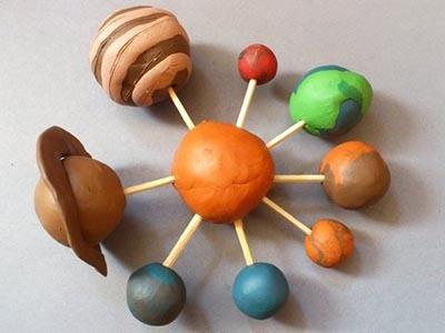 макет солнечной системой вместе с ребенком из пластилина